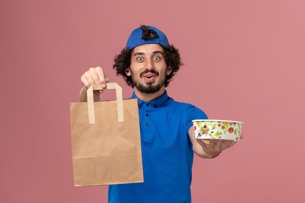 Курьер-мужчина, вид спереди в синей форме и плаще, держащий посылку с доставкой еды и миску на розовой стене, униформа службы доставки мужчин