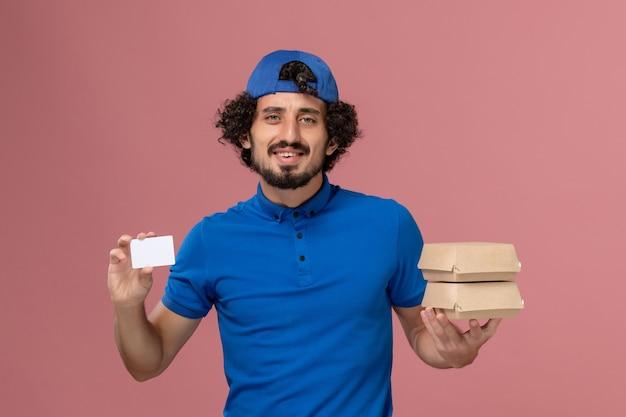 파란색 유니폼과 케이프 핑크 벽 유니폼 배달 남성 서비스에 카드로 배달 음식 패키지를 들고 전면보기 남성 택배
