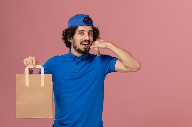 Вид спереди курьер-мужчина в синей форме и плаще, держащий бумажный пакет с едой на розовой стене, рабочая форма службы доставки