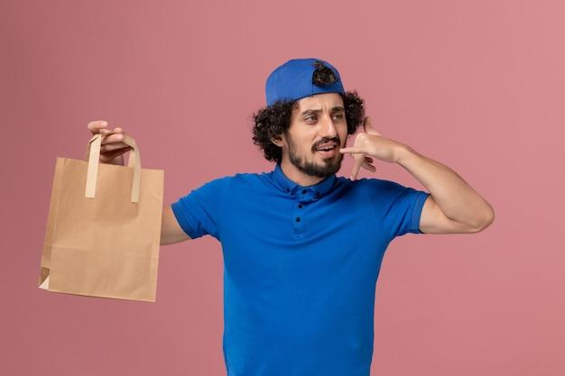 Вид спереди мужчина-курьер в синей форме и накидке, держащий бумажный пакет с едой на розовой стене