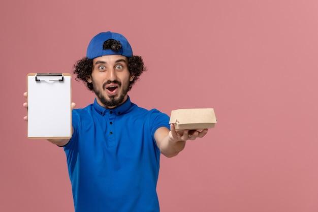 青い制服とケープの正面図男性宅配便は、ピンクの壁の制服配達ジョブサービスに小さな配達食品パッケージとメモ帳を保持しています