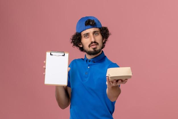 Вид спереди мужчина-курьер в синей форме и накидке, держащий небольшой пакет еды для доставки и блокнот на розовой стене, служба доставки униформы