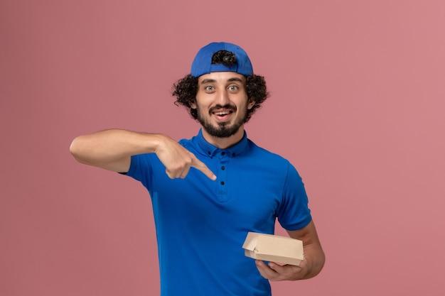 Курьер-мужчина, вид спереди в синей форме и плаще, держит небольшой пакет с доставкой на розовой стене