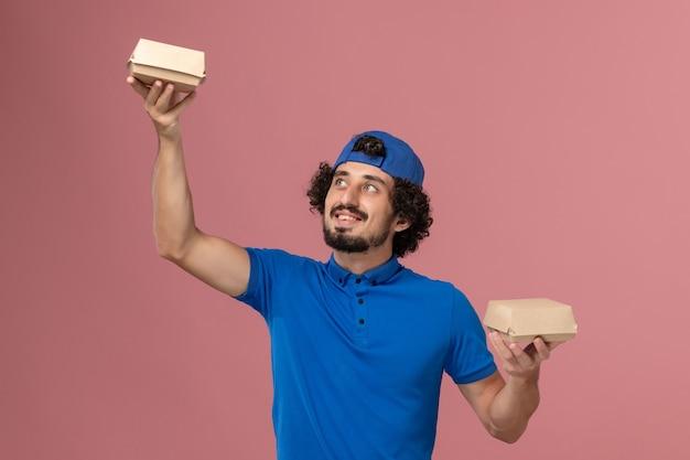분홍색 벽에 작은 배달 음식 패키지를 들고 파란색 유니폼과 케이프 전면보기 남성 택배