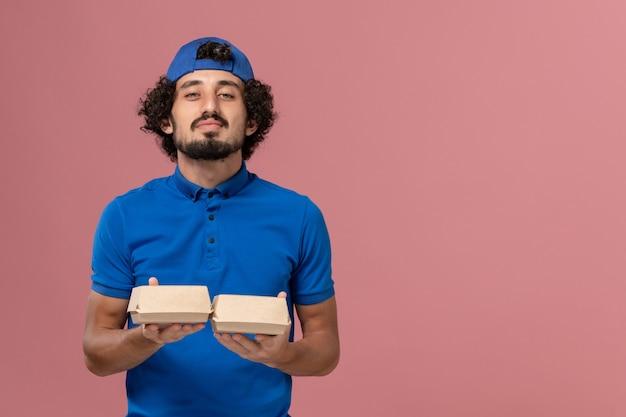 ピンクの壁に小さな配達食品パッケージを保持している青い制服と岬の正面図男性宅配便