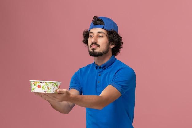 Курьер-мужчина, вид спереди, в синей форме и плаще, держит круглую миску для доставки на розовой стене