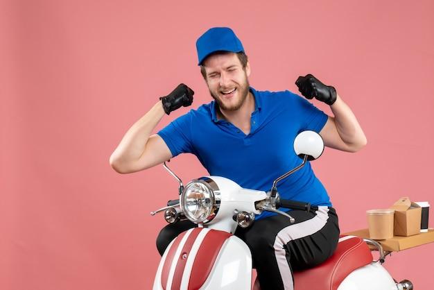 Курьер-мужчина в синей форме и перчатках на розовом цвете, вид спереди, служба доставки еды на велосипеде быстрого питания