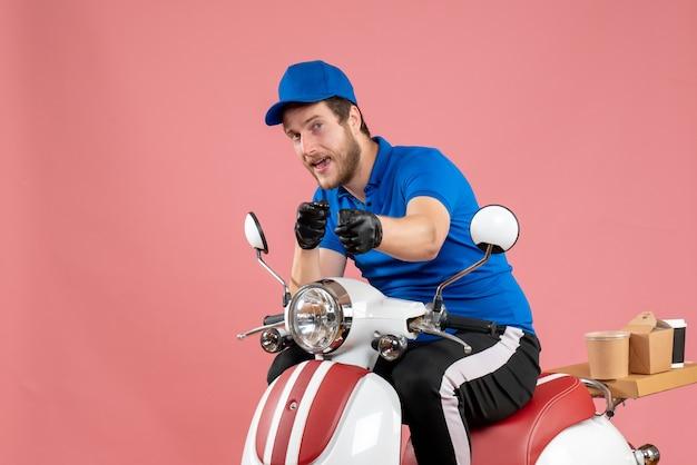Курьер-мужчина в синей форме и перчатках на розовом цвете, вид спереди, доставка работы на велосипеде быстрого питания