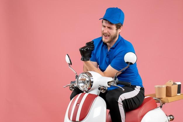 Вид спереди мужчина-курьер в синей форме и перчатках на розовом рабочем велосипеде по доставке еды в службу фаст-фуда