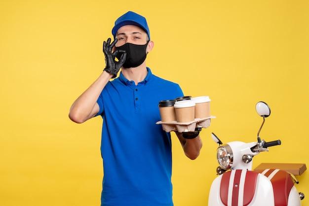 Курьер-мужчина в синей форме и маске, держащий кофе на желтой форме, вид спереди, пандемия доставки covid-work
