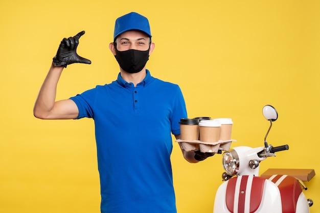 파란색 유니폼과 노란색 작업복 covid- 배달 유행성 직업 서비스에 커피를 들고 마스크에 전면보기 남성 택배