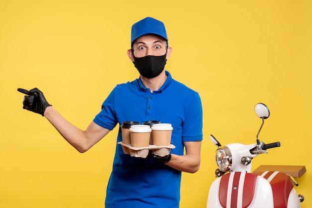 Курьер-мужчина в синей форме и маске, держащий кофе на желтой униформе, вид спереди, пандемия доставки ковид-работы