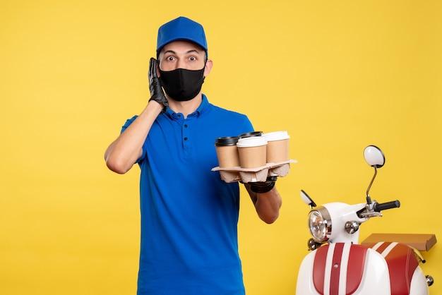 Курьер-мужчина, вид спереди в синей форме и маске с кофе на желтой униформе, служба занятости, пандемия доставки covid