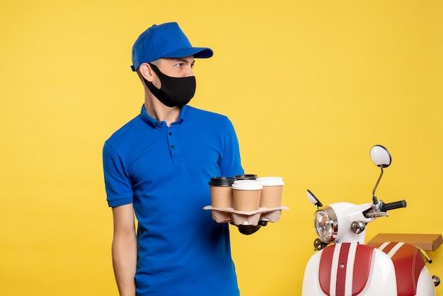 Курьер-мужчина в синей униформе и маске, держащий кофе на желтой униформе, вид спереди, пандемия ковид-работы