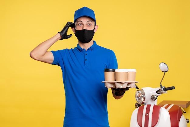 Курьер-мужчина, вид спереди в синей форме и маске, держащий кофе на желтой униформе, пандемия доставки covid-work