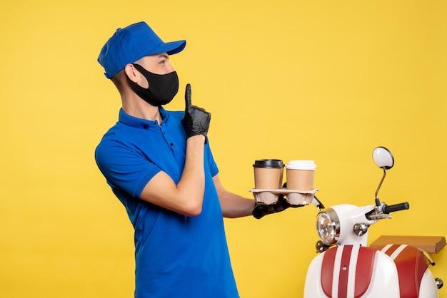 Вид спереди мужчина-курьер в синей форме и маске с кофе на желтой рабочей униформе служба работы covid-доставка пандемия