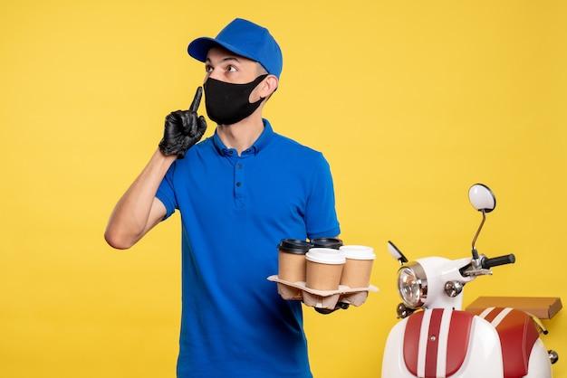 Вид спереди мужчина-курьер в синей форме и маске с кофе на желтой рабочей форме служба работы covid- delivery