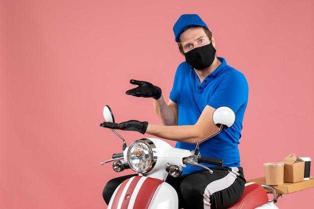 Вид спереди мужчина-курьер в синей униформе и маске на розовом вирусе, доставка на велосипеде, работа, служба быстрого питания, covid service, работа