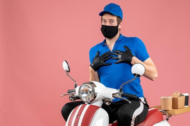 Вид спереди мужчина-курьер в синей форме и маске на розовом сервисе фаст-фуд covid- доставка вируса на велосипеде