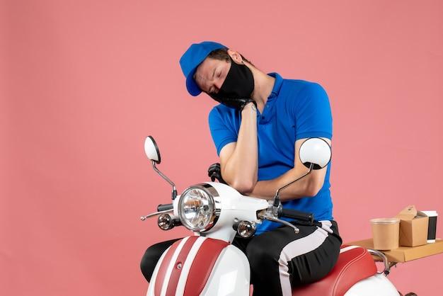 Вид спереди мужчина-курьер в синей форме и маске на розовом вирусе доставка на велосипеде работа фаст-фуд covid work