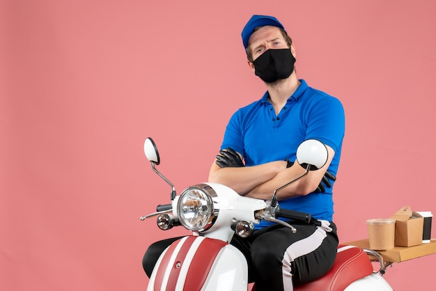 Вид спереди мужчина-курьер в синей форме и маске на розовом вирусе, доставка на велосипеде, работа службы быстрого питания
