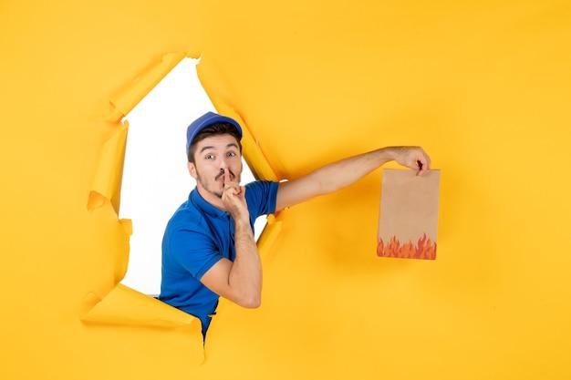 Курьер-мужчина, вид спереди в синей форме, дающий пакет с едой на желтом пространстве