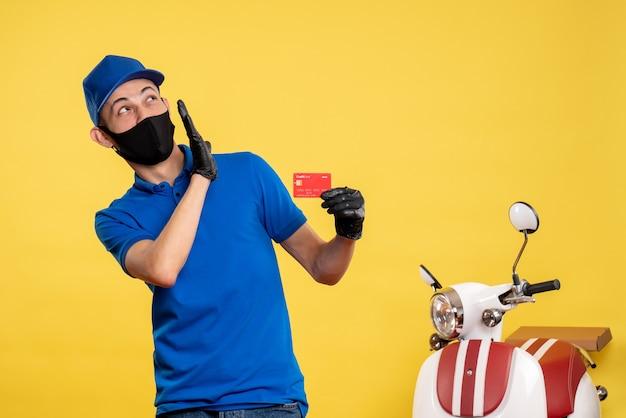 Курьер-мужчина в синей униформе, вид спереди, держит банковскую карту на желтой форме службы работы, цвет пандемии доставки covid-work