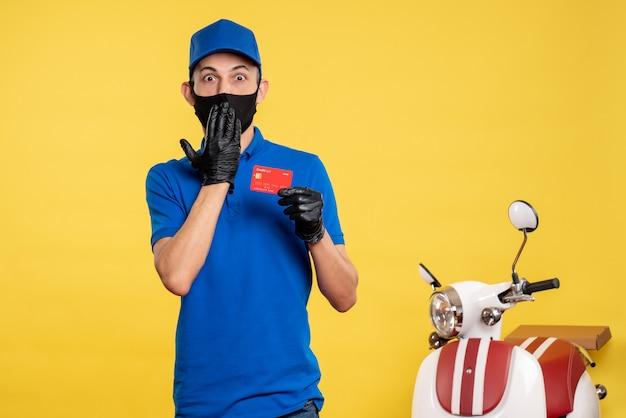 Вид спереди мужчина-курьер в синей форме с банковской картой на желтой форме службы работы, пандемия доставки covid-work