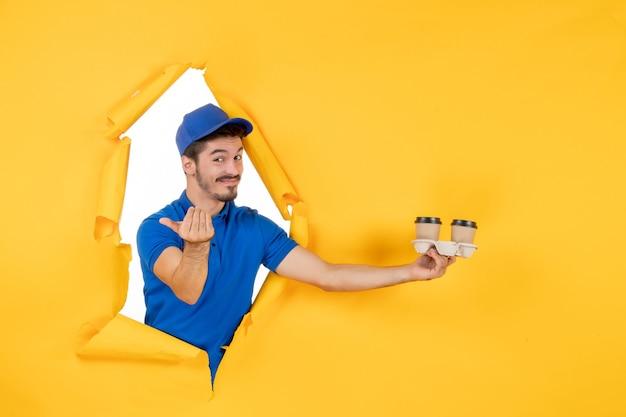 Курьер-мужчина в синей форме, держащий кофейные чашки на желтом пространстве, вид спереди