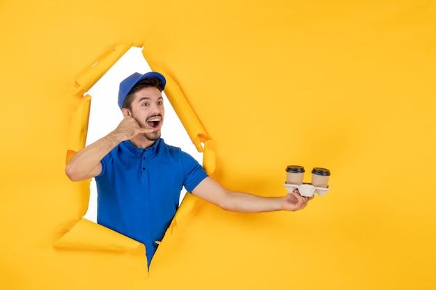 Вид спереди мужчина-курьер в синей форме, держащий кофейные чашки на желтом полу, доставка работы, цветной рабочий, работа, служба, фото