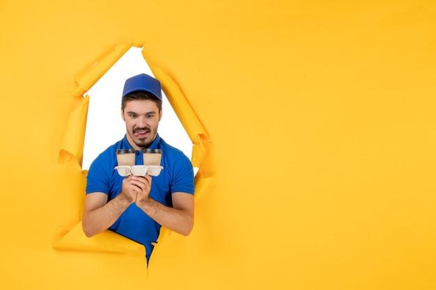 黄色のスペースにコーヒーカップを保持している青い制服の正面図男性宅配便