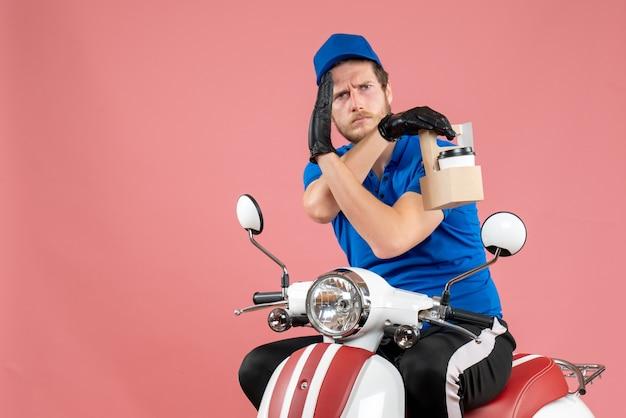 ピンクの仕事でコーヒーを保持している青い制服を着た正面の男性宅配便のファーストフード配達バイクサービスワーカーの色の仕事