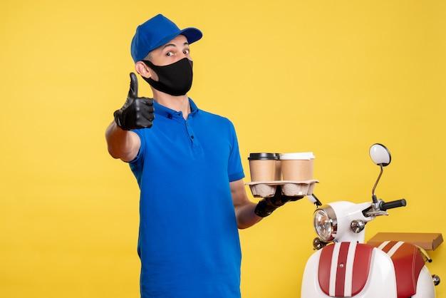 Курьер-мужчина в синей униформе, вид спереди, держит кофе на желтом цвете, служба вакансий, covid-пандемия, доставка работы