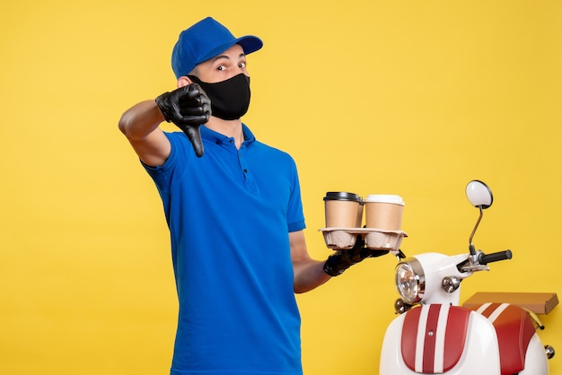 Вид спереди мужчина-курьер в синей форме держит кофе на желтой униформе, цветная служба работы, доставка на работу при пандемии.