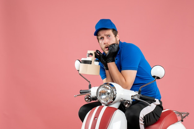 ピンクの仕事の色のファーストフードの仕事の配達バイク サービス ワーカーにおびえたコーヒーを保持している青い制服を着た正面の男性宅配便