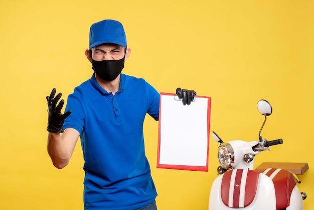 Курьер-мужчина в синей форме, вид спереди, держит заметку о желтой работе службы занятости, цвет пандемии доставки работы
