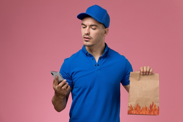 ピンクの壁に食品パッケージと電話を保持している青い制服の正面図男性宅配便、仕事の制服サービス配達労働者