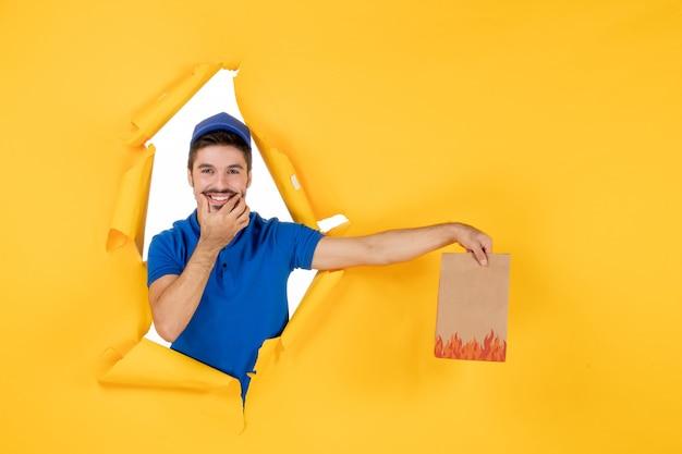 Курьер-мужчина в синей униформе, улыбаясь в желтом пространстве, держит пакет с едой