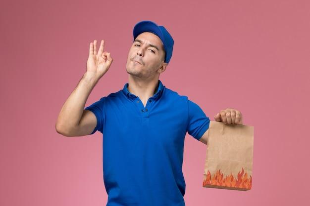 ピンクの壁に食品パッケージを保持している青い制服の正面図男性宅配便、労働者の制服サービスの提供