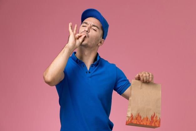 ピンクの壁に食品パッケージを保持している青い制服の正面図男性宅配便、ジョブワーカーの制服サービスの提供