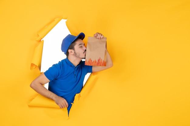 Курьер-мужчина в синей форме, держащий пакет с едой на желтом пространстве, вид спереди