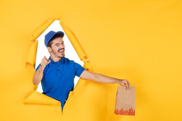 黄色のスペースに食品パッケージを保持している青い制服の正面図男性宅配便