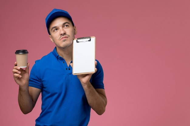 ピンクの壁に小さなメモ帳とコーヒーを保持している青い制服の正面図男性宅配便、労働者の制服サービスの提供