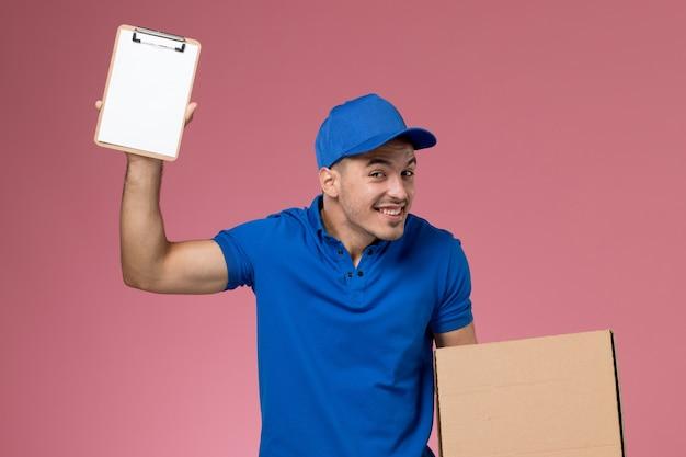 ピンクの壁に小さなメモ帳とフードボックスを保持している青い制服の正面図男性宅配便、労働者の制服サービスの提供