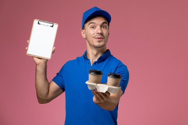 Вид спереди мужской курьер в синей форме, держащий блокнот с кофе на розовой стене, доставка униформы рабочего места