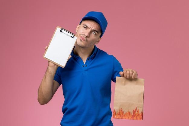ピンクの壁にメモ帳を保持している青い制服の正面図男性宅配便、労働者の制服サービスの提供