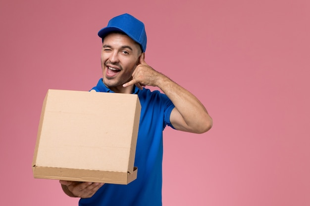 Курьер-мужчина, вид спереди в синей форме, держит открывающуюся коробку для доставки еды на розовой стене, единообразная доставка услуг