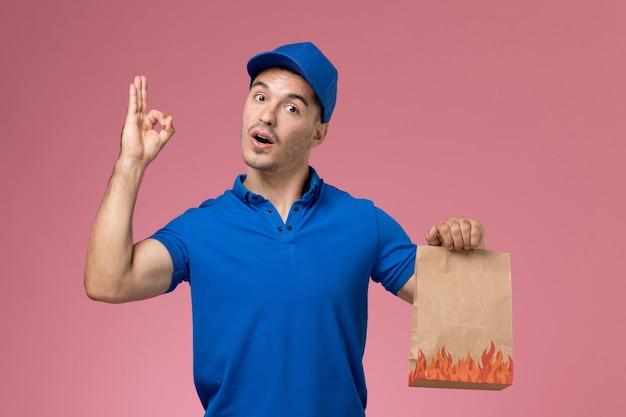ピンクの壁に紙の食品パッケージを保持している青い制服の正面図男性宅配便、労働者の制服サービスの仕事の配達