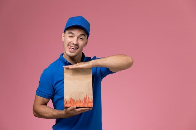 ピンクの壁にウィンクする食品の紙のパッケージを保持している青い制服の正面図男性宅配便、労働者の制服サービスの提供
