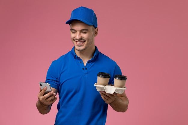 Вид спереди мужской курьер в синей форме, держащий телефон и кофейные чашки на розовой стене, доставка униформы рабочего места